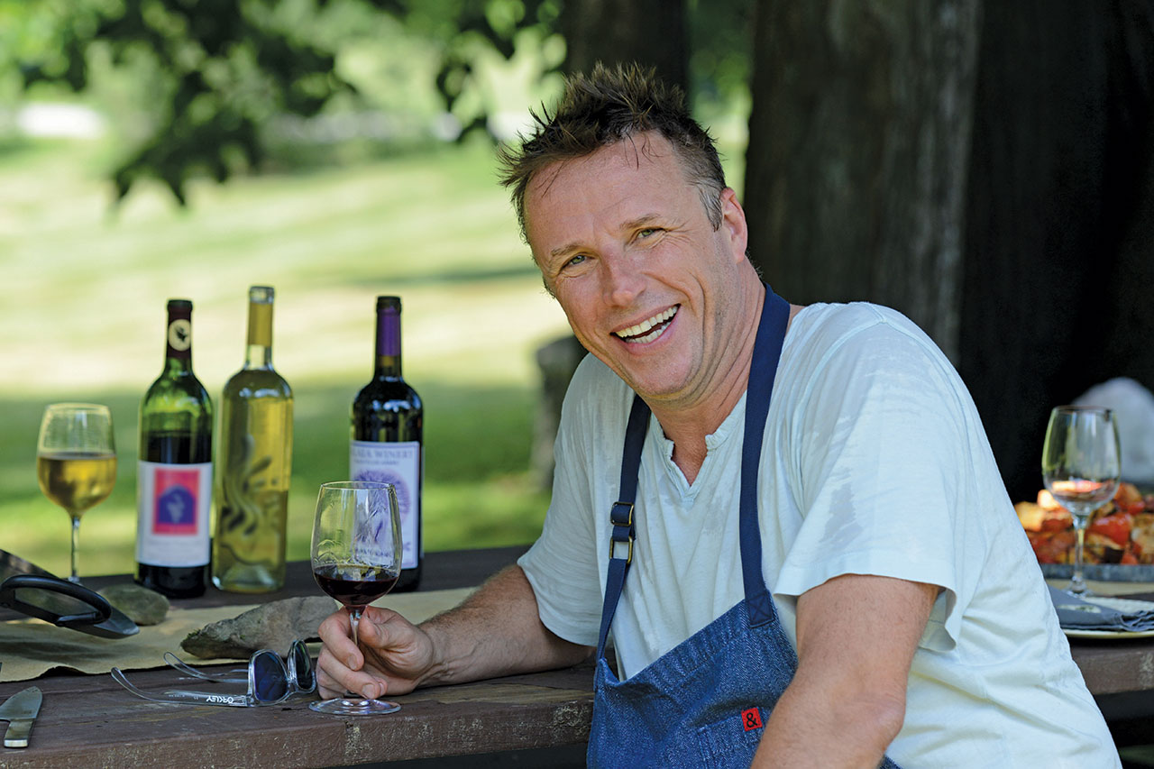 man sitting at picnic table with glass of wine