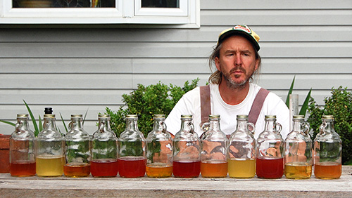 man looking at glass bottles filled with different colored ciders lined up on a table